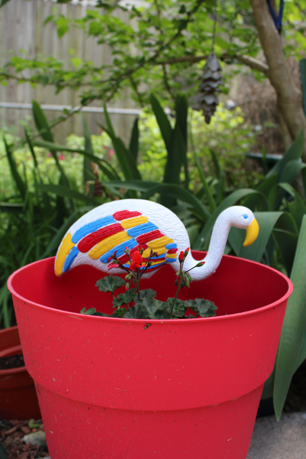 red, white, blue and yellow flamingo in a red planter with flowers
