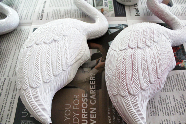 two white flamingos on newspaper