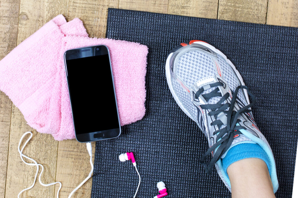 a smartphone with earbuds plugged in sitting on a yoga mat next to a foot in a sneaker