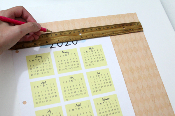 hand tracing a ruler edge onto a pink paper