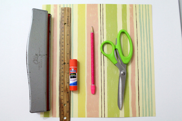 green and yellow striped scrabook paper, scissors, a pencil, glue stick, ruler, and hole punch