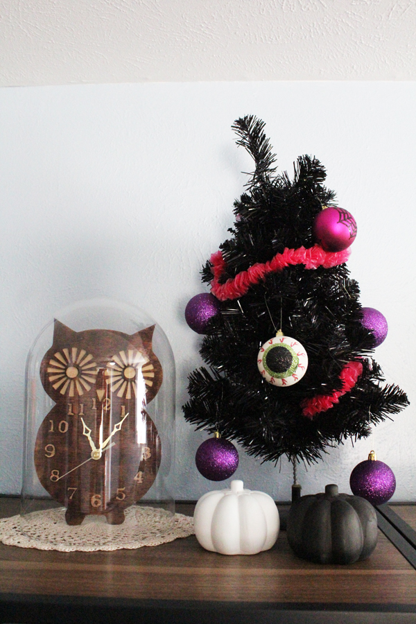 miniature black Christmas tree decorated with pink glittery ball ornaments and eyeballs