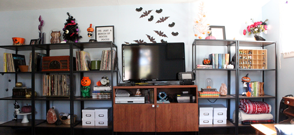 television on a stand surrounded by open shelves filled with books, records, and Halloween knick-knacks