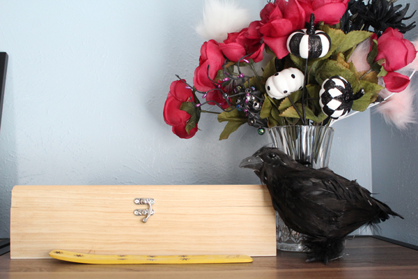 black faux crow sitting next to a vase of silk flowers in pink and black