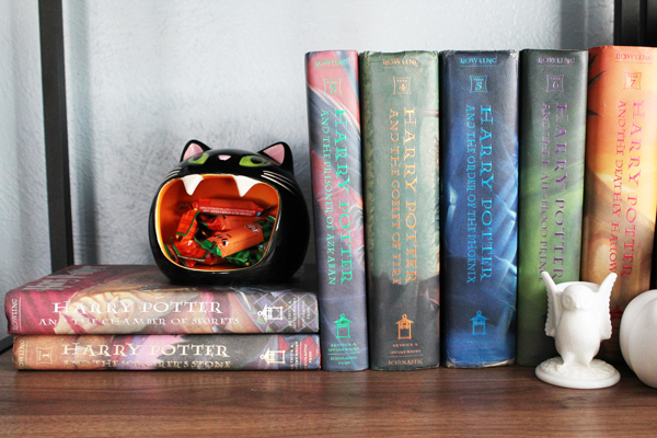 hardback Harry Potter books on a shelf with a black Halloween cat holding candy in its open mouth