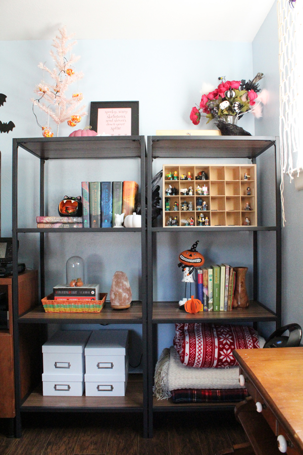 open shelving with Halloween knick-knacks, books, boxes, and other decor
