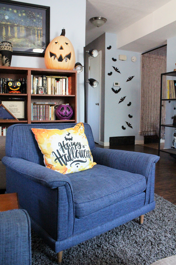living room area with a vintage blue chair, Halloween throw pillow, and vintage Halloween decor on the shelf behind it