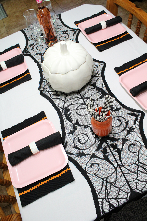 Aerial view of dining table with a white tablecloth, spiderweb table runner, pink plates, black napkins, and a white pumpkin cookie jar