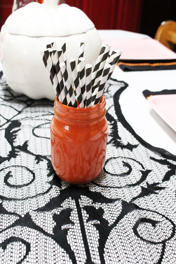orange painted mason jar with black and white striped paper straws on a black and white table