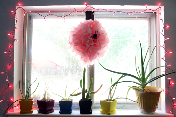 window lined with pink fairy lights and a pink pompom hanging in the center