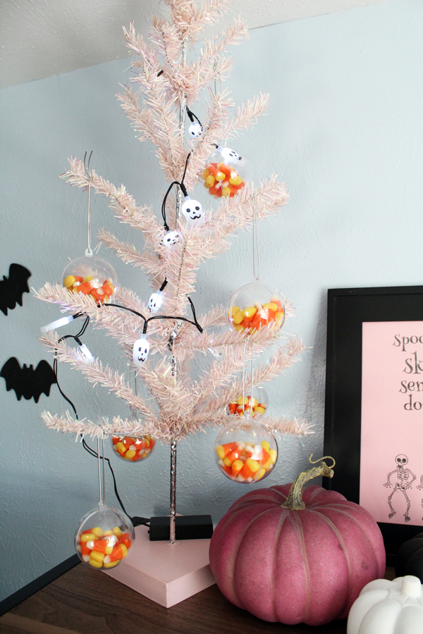 18-inch tall pink Christmas tree decorated with skeleton lights and candy corn ornaments