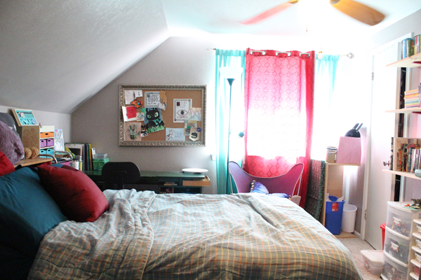 bedroom with blue bedding, a green desk, and blue and red curtains