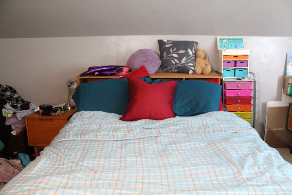 bed with blue plaid blanket, blue and red pillows, and clutter on the headboard