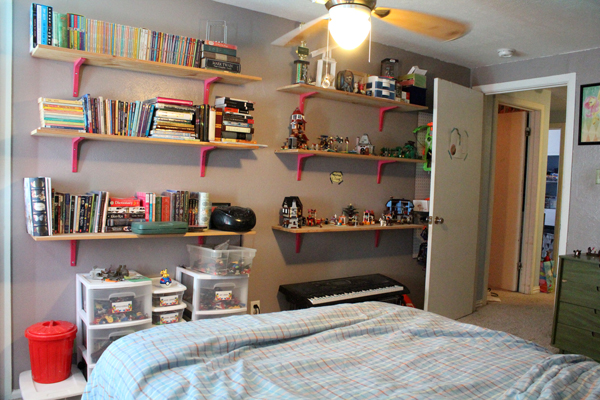 wall shelves stuffed with books, a stereo, LEGO constructions, and odd clutter