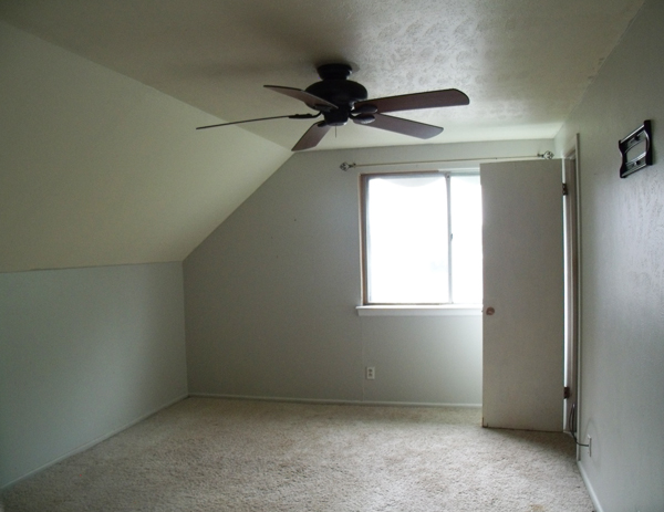 empty bedroom with dingy gray walls and brown carpet