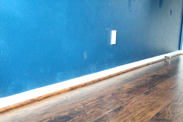 blue wall and brown floor finish with hickory brown quarter-round trim