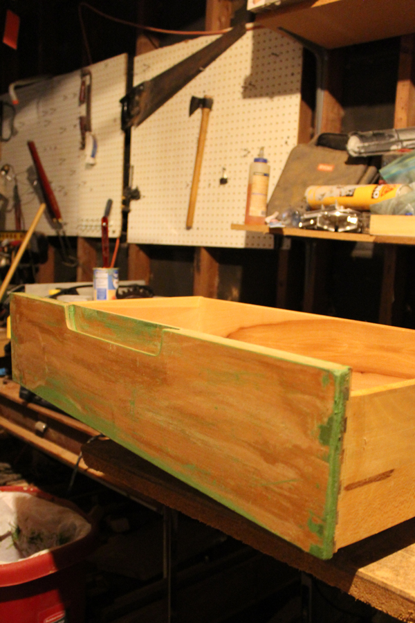 a natural wooden dresser drawer sitting on a workbench with remnants of green paint around the edges