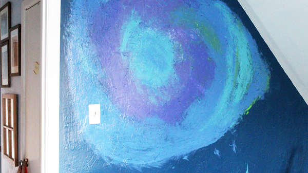 a dark blue wall with light blue, purple, and green paint swirled like a galaxy