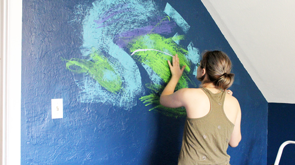 person spreading blue and green paint on a dark blue wall
