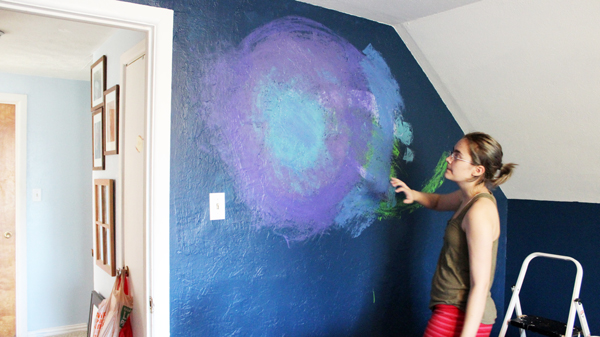 person spreading blue paint on a purple and blue wall
