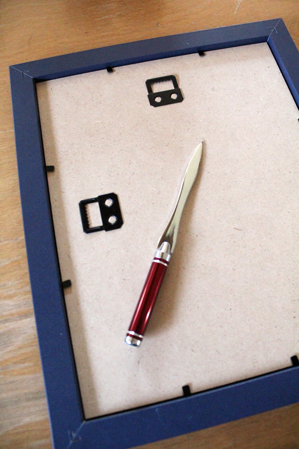 a letter opener sitting on the back of a picture frame with metal clips