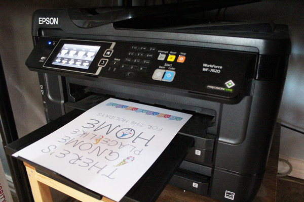 the printable Christmas gnome artwork coming out of an inkjet printer