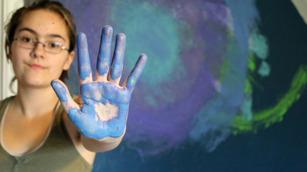 person with blue and purple paint on one hand standing in front of a painted mural