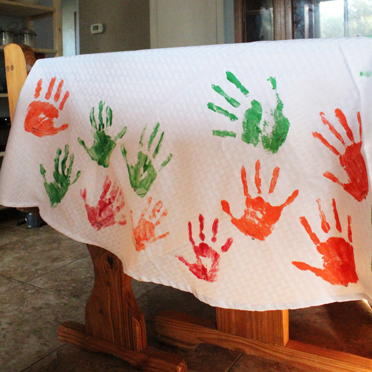 white tablecloth with handprints in green, red, and orange paint