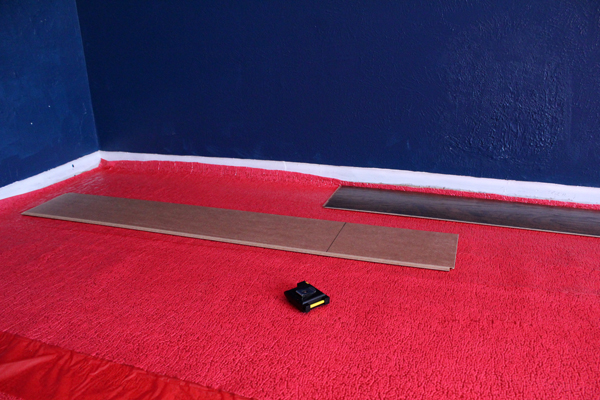 hickory brown laminate wood boards sitting on the red underlayment