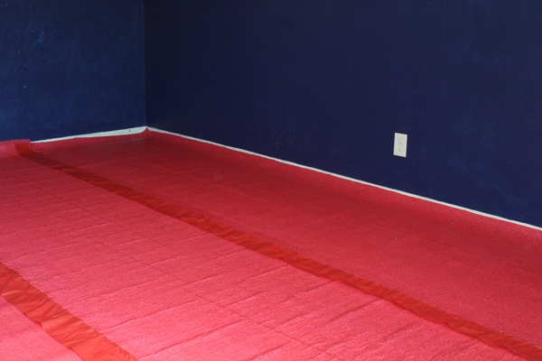 red underlayment covering the floor with blue walls in the background
