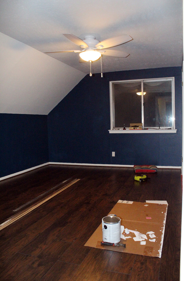 bedroom with finished dark brown laminate floor and dark blue walls