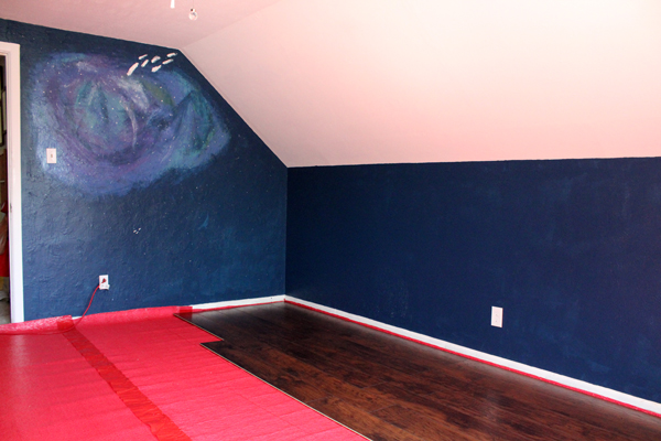 a room with laminate flooring covering a large section of the red underlayment