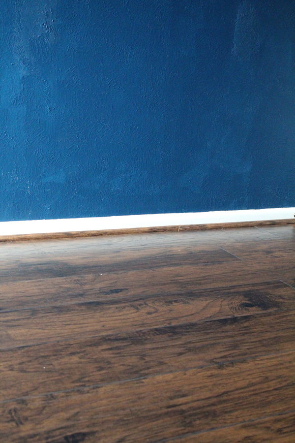 finished wood laminate flooring and dark blue walls