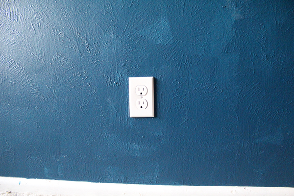 closeup of dark blue wall with modern white outlet