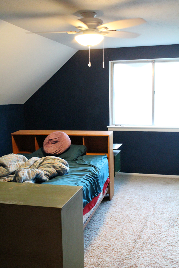 bedroom with dark blue walls, dingy white carpet, and furniture pushed to the center of the room