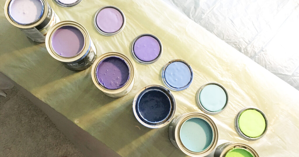 six open paint containers lined up in a row from purple to blue to green