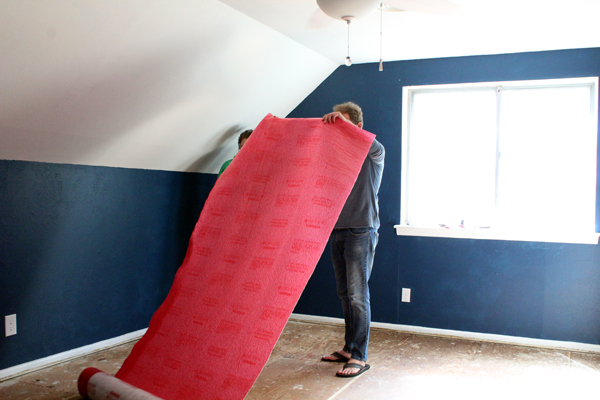 people rolling out a large piece of red underlayment onto the subflooring