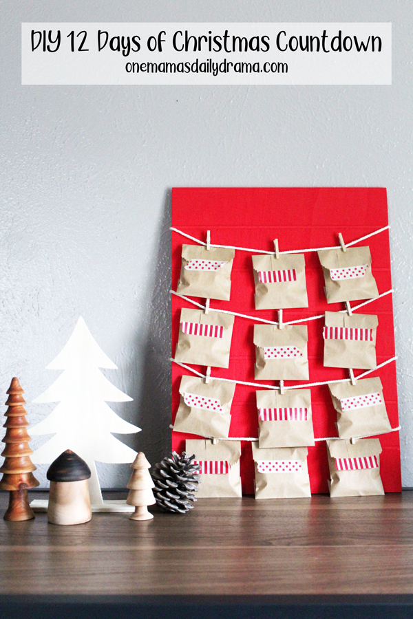 Christmas countdown calendar made from a red painted board with brown paper envelopes sealed with washi tape