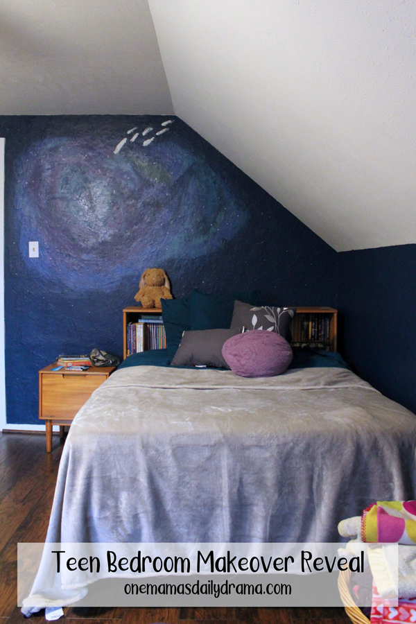 bedroom corner with blue space mural and blue and gray bedding on a vintage bed