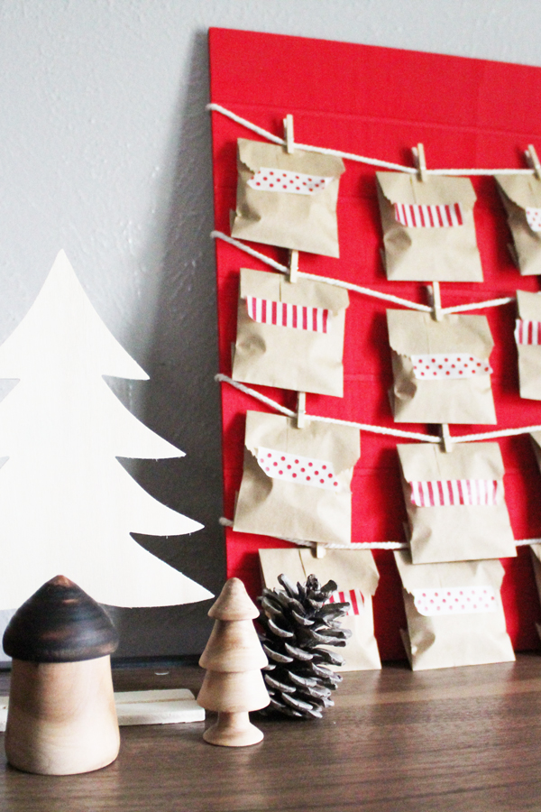 red Christmas countdown calendar with brown paper envelopes beside a small wooden tree