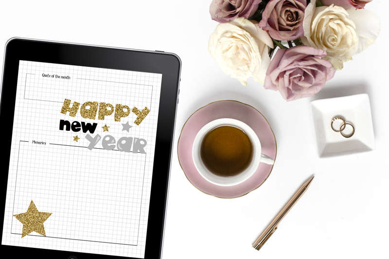 iPad with New Year's bullet journal page beside a mug of tea and a pen