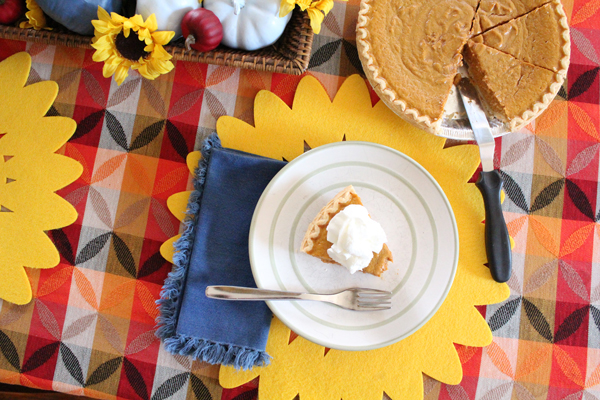 slice of pie with whipped cream beside a whole pie on a colorful red and yellow table