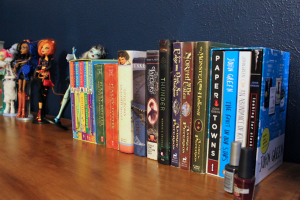 a dozen books lined up on a dresser, including Harry Potter and John Green