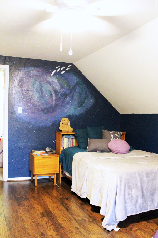 full sized vintage bed with turquoise and gray bedding against a blue and purple galaxy wall mural