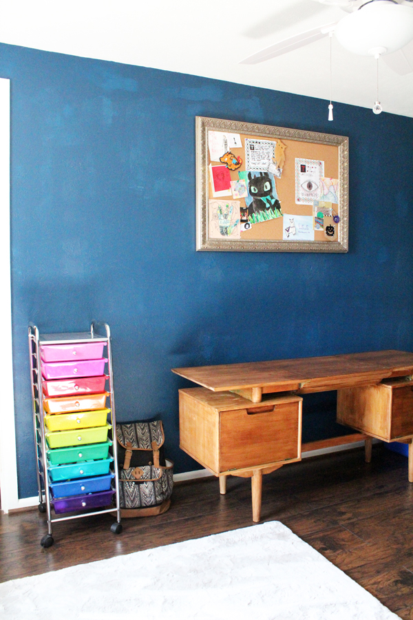 workspace with a rolling cart, wooden desk, and bulletin board