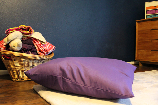 purple floor pillow beside a basket of blankets