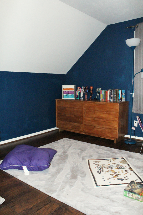 medium gray area run in front of an 8-drawer dresser in a corner of a blue room