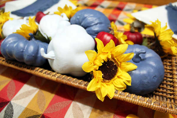 sunflowers and pumpkins in a basket on a checkered tablecloth