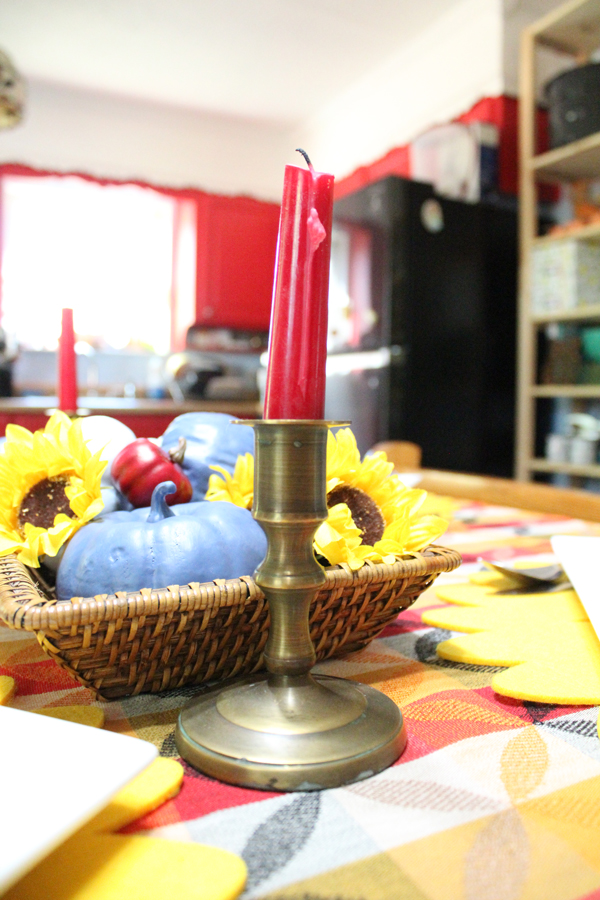 a red taper candle in a nickel candleholder