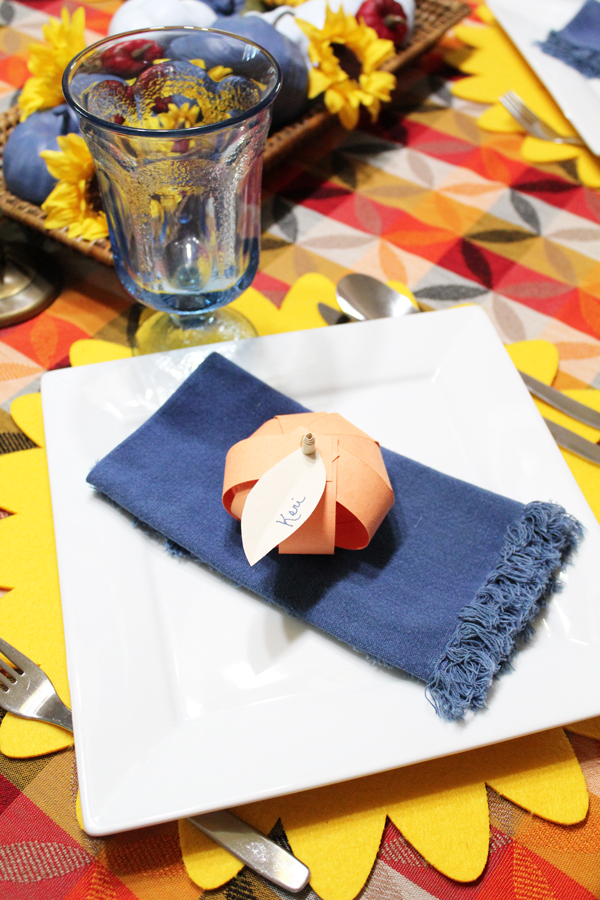 "paper pumpkin with the name ""Keri"" written on the leaf sitting on a blue napkin on a white plate"